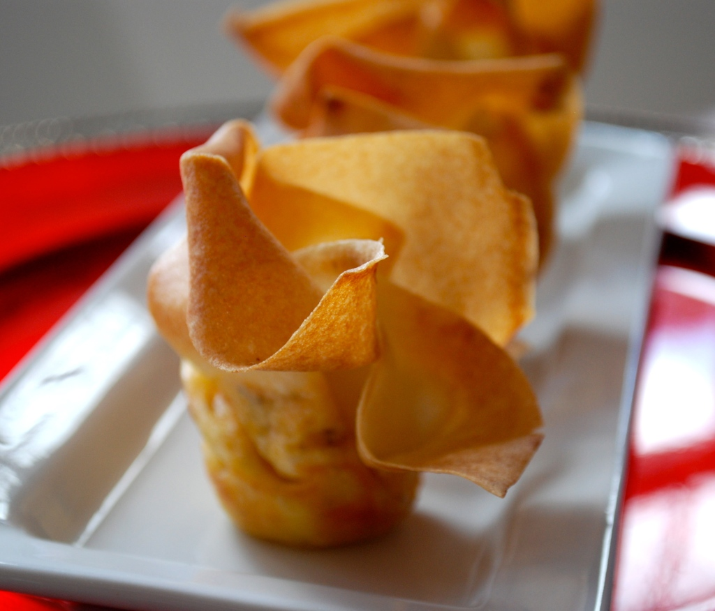 A baked spring roll purse on a white plate filled with goat and cheddar cheese.