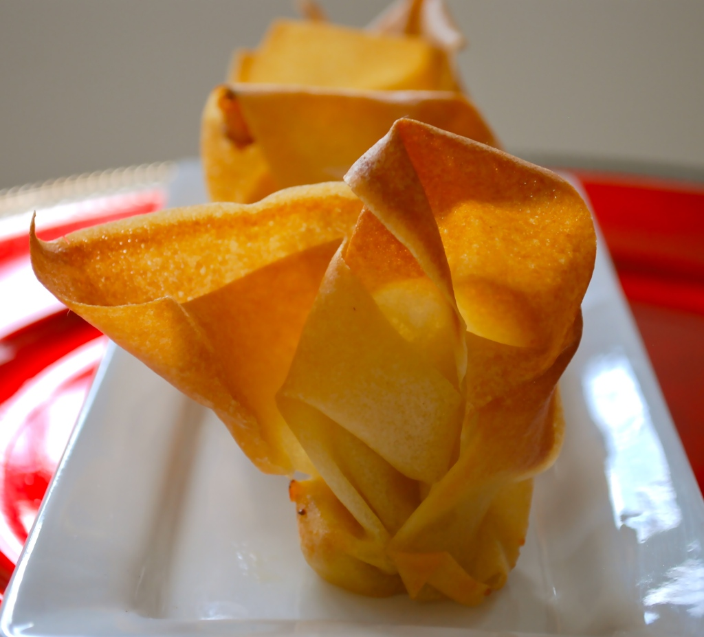 Close up of a baked spring roll purse on a white plate filled with goat and cheddar cheese.
