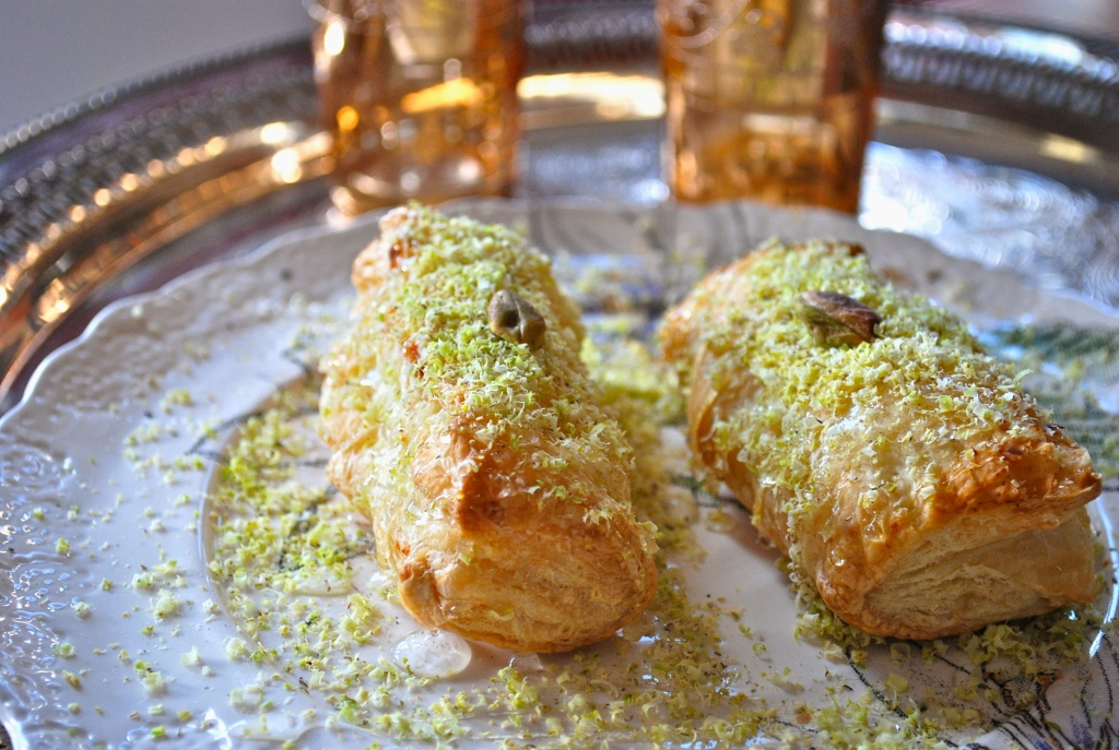 Two sweet bourekas on a white plate with orange blossom drizzle and pistachio crumble and one whole shelled pistachio on top of each.