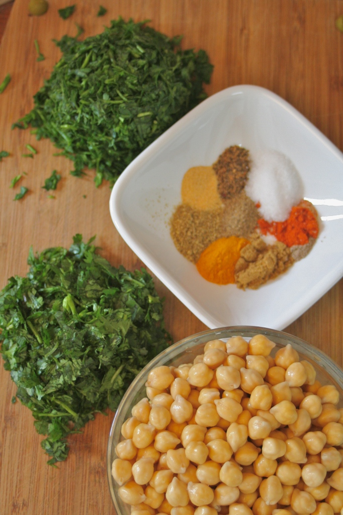 Display of ingredients to make baked green falafel. Chopped cilantro, chopped parsley , a bowl of chickpeas and a spice mix