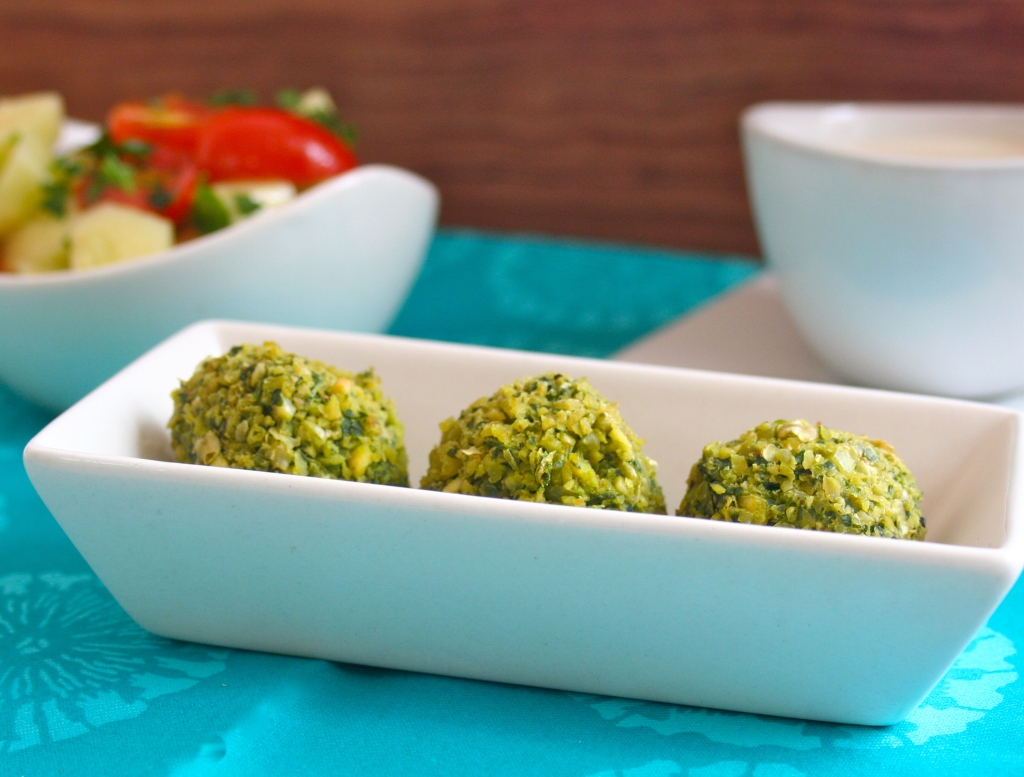 3 baked green falafel bowl in a rectangular dish. On the background there is a bowl of cucumber and tomato salad and a bowl of tahini sauce