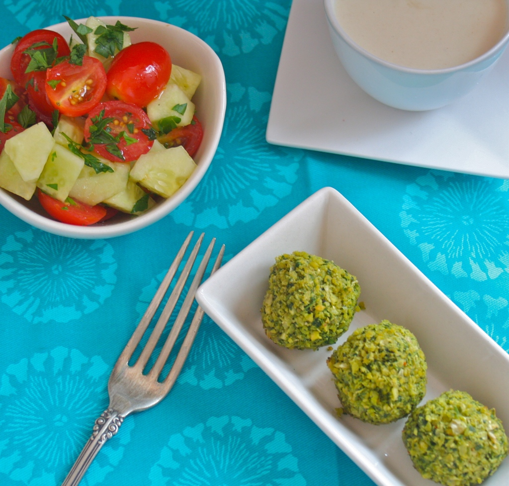 3 baked green falafel bowl in a rectangular dish with a bowl of cucumber and tomato salad and a bowl of tahini sauce