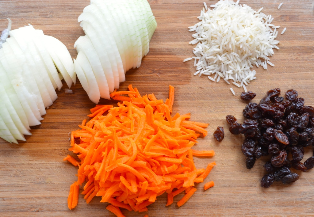 Rosh Hashanah Sweet Basmati Rice with Carrots & Raisins - On a cutting board, sliced onions, shredded carrots, basmati rice and raisins