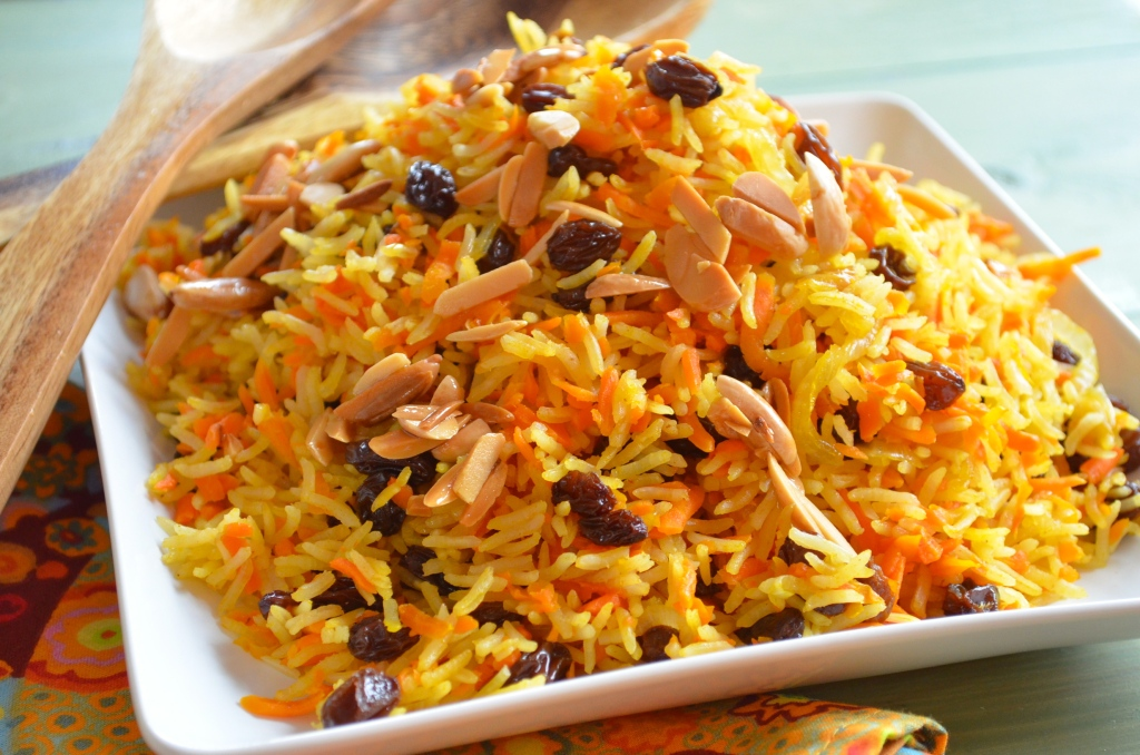 A square place with rice and carrots raisins and toasted almonds on top. On the background 2 wooden spoons
