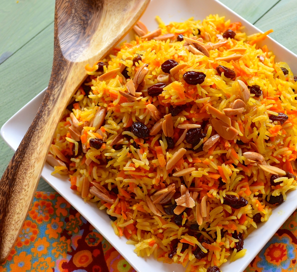 A square plate with a mountain of Rosh Hashanah Sweet Basmati Rice with Carrots & Raisins with toasted almonds on top. One wooden spoon on the side of the dish. Birds eye view