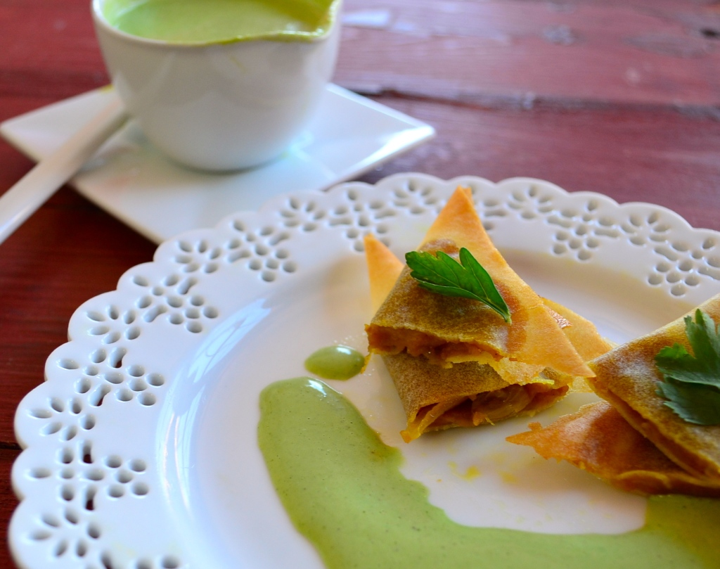 Pumpkin appetizer on a white plate with a fresh herb sauce